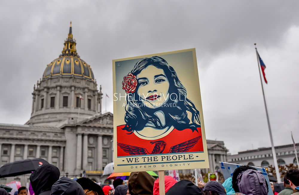 """Artist Shepard Fairey's sign """"We the People Defend Dignity,"""" portraying a Latina in red, is held high in protest at the rally before San Francisco Womens March with City Hall in the background. Credit: Shelly Rivoli"""