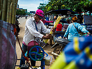 05 JULY 2017 - POIPET, CAMBODIA:  A sugar cane juice vendor in Poipet crushes sugar cane to make juice for Cambodian migrant workers returning from Thailand. The Thai government proposed new rules for foreign workers recently. The new rules include fines of between 400,000 and 800,00 Thai Baht ($12,000 - $24,000 US) and jail sentences of up to five years for illegal workers and people who hire illegal workers. Hundreds of companies fired their Cambodian and Burmese workers and tens of thousands of workers left Thailand to return to their countries of origin. Employers and human rights activists complained about the severity of the punishment and sudden implementation of the rules. On Tuesday, 4 July, the Thai government suspended the new rules for 180 days and the Cambodian and Myanmar governments urged their citizens to stay in Thailand, but the exodus of workers continued through Wednesday.    PHOTO BY JACK KURTZ