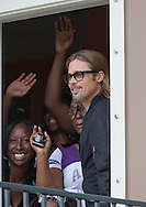 """Brad Pitt with residents in their home in the"""" Make it Right """" housing project he developed in New Orleans Lower 9th Ward the day before a star-studded gala being held in New Orleans."""