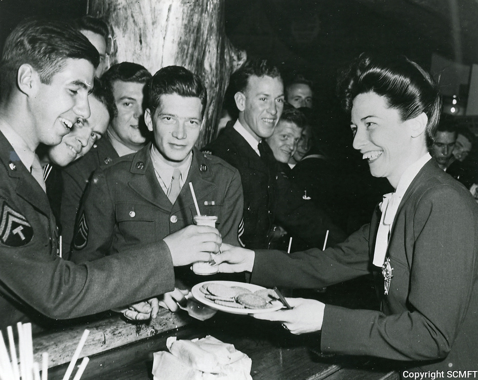 1944 Actress, Cass Daley serves milk and cookies to serviceman at the Hollywood Canteen.