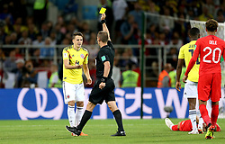 Referee Mark Geiger shows Colombia's Santiago Arias a yellow card for a foul on England's Harry Kane (right, floor) during the FIFA World Cup 2018, round of 16 match at the Spartak Stadium, Moscow.