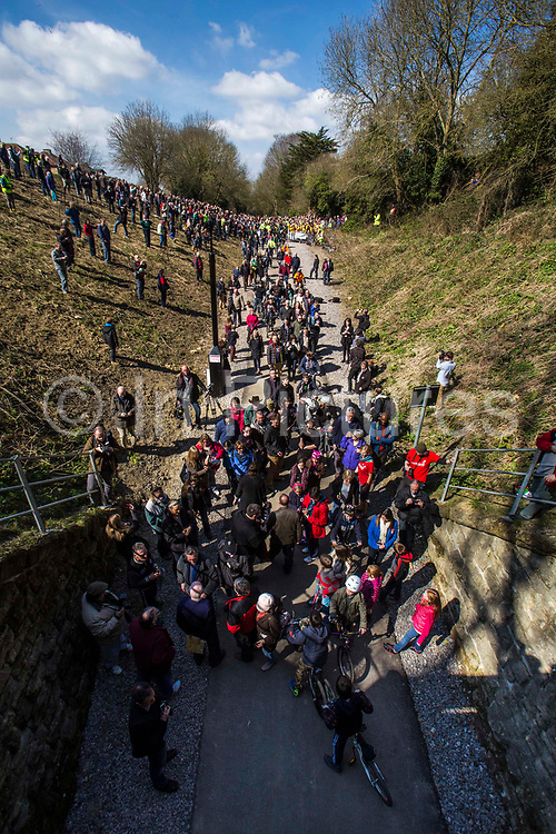 A large group of people gather at the entrance of the Devonshire Tunnel for the official opening of the Bath Two Tunnels Greenway on 6th April 2013.  The 13 mile shared-path is a dramatic and accessible route leading south from Bath city and is accessible by foot, cycle, buggy and wheelchair. This development was started by a local community group and is part of the Sustrans lottery-funded project, Connect 2 Cycling Network. Sustrans is a charity that works with communities, policy-makers and partner organisations so that people can choose healthier, cleaner and cheaper journeys and enjoy better, safer spaces to live in. The event was attended by hundreds of cyclists and pedestrians of all ages and abilities. Bath, Somerset, United Kingdom.