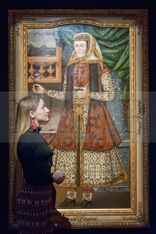 """© Licensed to London News Pictures. 20/10/2017. London, UK. A staff member views """"A Portrait of a Lady holding a rose and glass"""", Persia, circa 1660-1700, (Est. GBP0.8-1.0m), at a preview of Islamic, Middle Eastern and other artworks which be auctioned at Sotheby's New Bond Street on 24 and 25 October. Photo credit : Stephen Chung/LNP"""