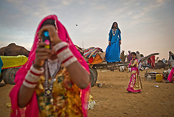 Sunita Devi, 13, right and Subita Devi, 13 take photos on their mobile phone at the world's largest annual cattle fair in the desert town of Pushkar, in the Indian state of Rajasthan. Every year thousands of camel herders from the semi-nomadic Rabari tribe, who make a living rearing animals, travel for two to three weeks across 500 kilometers to set up camp in the desert dunes near Pushkar to sell their livestock. The herders sell more than 20,000 camels, horses and other animals at the annual cattle fair.