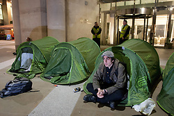 © licensed to London News Pictures. London, UK 01/05/2012. A demonstrator sitting in his tent outside London Stock Exchange as Occupy London activists occupy parts of the London Stock Exchange and Paternoster Square as part of May Day protests in London. Photo credit: Tolga Akmen/LNP