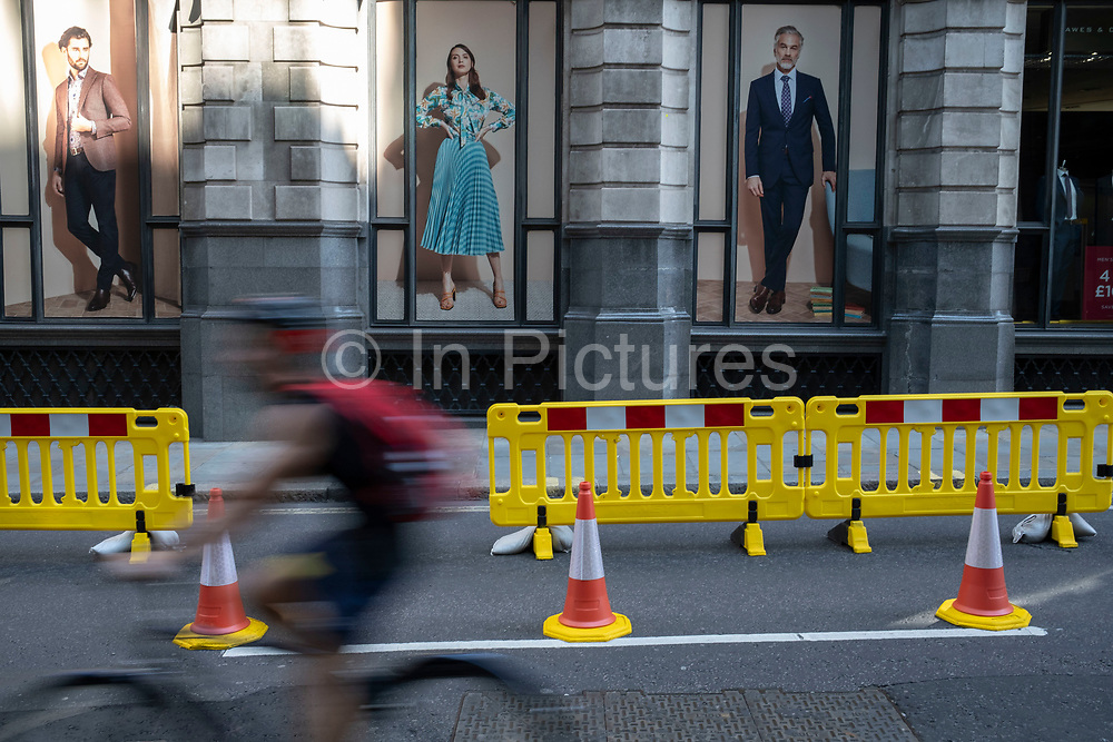 In the City of London, large fashion advertising posters loom high over yellow barriers which are placed to mark out new road layouts for social distancing on the day that it was announced that the Coronavirus lockdown measures are set to ease even further and the quiet city starts coming to an end, on 23rd June 2020 in London, England, United Kingdom. As of today the government has relaxed its lockdown rules, and is allowing some non-essential shops to open with individual shops setting up social distancing queueing systems.