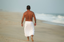 back of man in a white towel walking on a deserted beach