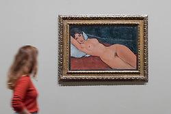 """© Licensed to London News Pictures. 21/11/2017. London, UK.  A staff member walks by """"Reclining Nude on a White Cushion"""", 1917. Preview of """"Modigliani"""", the most comprehensive exhibition of works by Amedeo Modigliani ever held in the UK.  On display are iconic portraits, sculptures and 12 nudes, the largest group ever shown in the UK.  The show runs 23 November to 2 April 2018.  Photo credit: Stephen Chung/LNP"""
