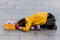 Girl begging on the sidewalk, Beijing Middle Road, Lhasa, Tibet (Xizang), China.