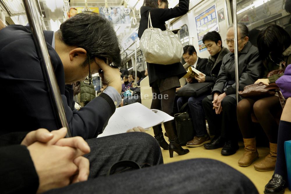 businessman reading paperwork while commuting Tokyo Japan