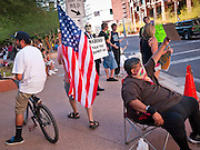 16 OCTOBER 2011 - PHOENIX, AZ: An Occupy Phoenix protester carries an American flag through downtown Sunday. About 200 people continued the Occupy Phoenix protest in downtown Phoenix Sunday afternoon. The protest peaked Saturday afternoon at about 2,000 people. Nearly 50 people were arrested late Saturday night on misdemeanor trespassing charges when they tried to camp in a park near downtown and on Sunday the crowd dwindled to 200. Protesters hope to continue the protest through Monday by marching around downtown and picketing banks in the area.    PHOTO BY JACK KURTZ
