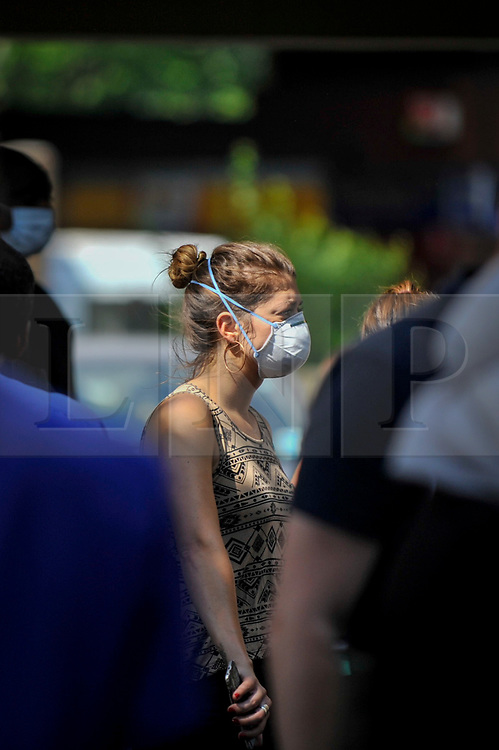 © Licensed to London News Pictures. 14/06/2017. London, UK.   A woman wears a face mask as protection against the acrid smell of burning from The Grenfell Tower, near Latimer Road in west London, which was engulfed in a huge fire the previous night, resulting in at least twelve fatalities with many more in critical condition. Photo credit : Stephen Chung/LNP