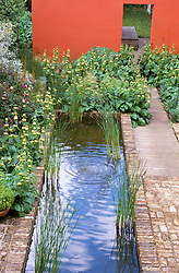 Canal on the terrace with orange wall dividing two sections of the garden. Planting includes Phlomis samia and Eremurus x isabellinus 'Cleopatra'. Design: Dan Pearson