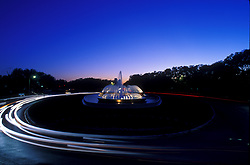 Stock photo of the Mecom Fountain in downtown Houston at night with passing cars