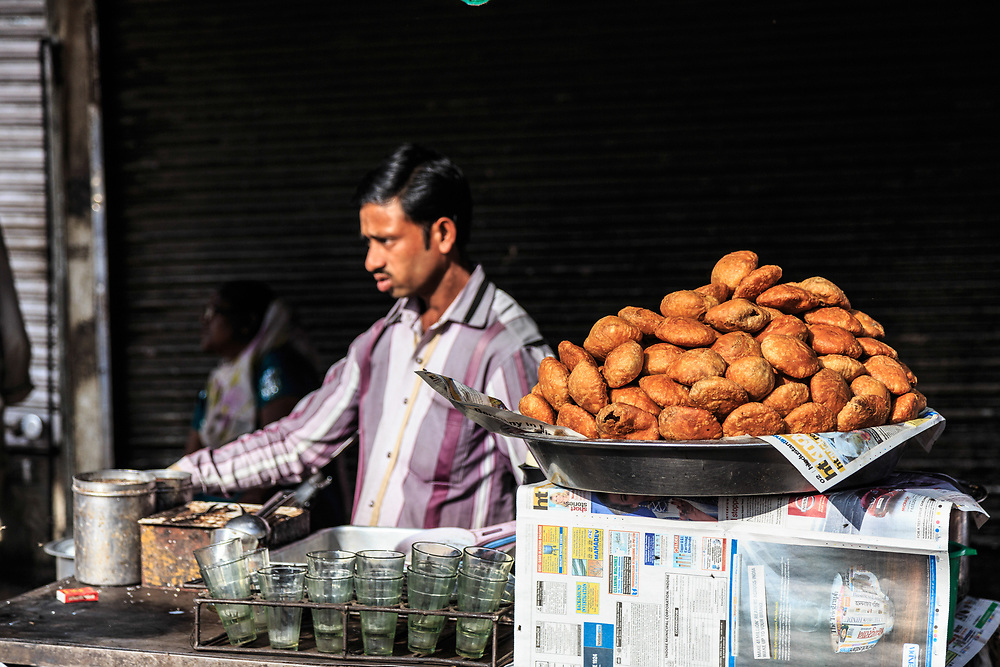 Kachori for sale in Old Town in New Delhi, India. Kachori is a popular spicy snack from the Indian subcontinent. It is usually a round flattened ball made of fine flour filled with a stuffing of baked mixture of yellow moong dal or Urad Dal (crushed and washed horse beans), besan (crushed and washed gram flour), black pepper, red chili powder, salt and other spices.