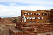 Jack Russell Terrier in front of the sign at the entrance of the Captiol Reef National Park located outside of Torrey, UT, United States