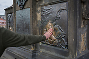 A hand reaches out to touch and help polish part of the statue of St John Nepomuk on Charles Bridge,  on 18th March, 2018, in Prague, the Czech Republic.