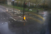 Aerial view through misted bus window of traffic bollard during seasonal downpour of rain.