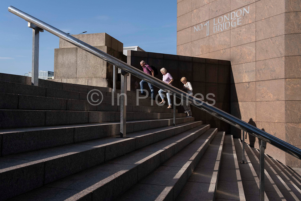 In the week that many more Londoners returned to their office workplaces after the Covid pandemic and the summer holidays, commuters and visitors use the stairs at the southern end of London Bridge in Southwark, on 8th September 2021, in London, England.