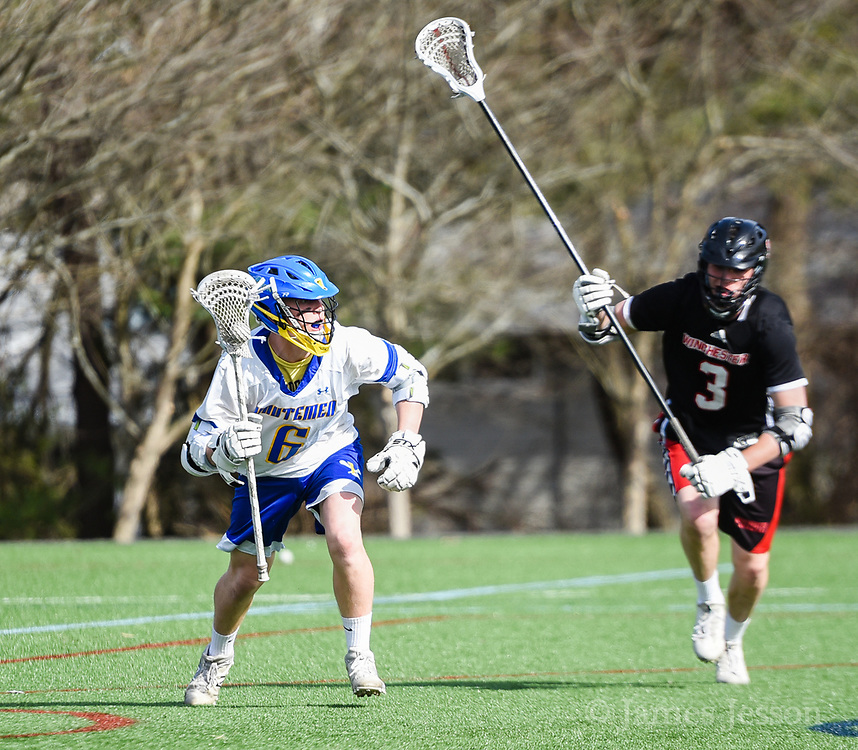 Lexington High School junior Nate Sidel handles the ball under pressure from Winchester High School junior Hayden Bean during the game in Lexington, April 24, 2018. Winchester won the game, 11-6.   [Wicked Local Photo/James Jesson]