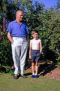 Family portrait full length grandfather and grandson standing in garden, British culture 1967 both wearing slippers