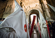 Hooded members of a brotherhood exit from the Cathedral of Granada at night. Andalusia, Spain