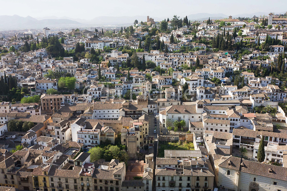 Aerial landscape of old Arab Albaicin quarter and surrounding barrios of the Moorish city of Granada. This aerial landscape also shows in the foreground, the old Arab Albaicin quarter and surrounding barrios of Moorish city of Granada. The Albaicin Quarter is the old Moorish quarter across the River Darro from the Alhambra. When the Moors controlled Granada, this area of the city was the most densely populated. The streets are narrow and many of them do not have sidewalks. The houses are not very high and they are very close to each other. Alhambra (in Arabic, Al-Ḥamra) is a palace and fortress complex constructed during the mid 14th century by the Moorish rulers of the Emirate of Granada in Al-Andalus.