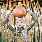 Mursi tribal woman carrying a water gourd on her head, Omo Valley, Southern Ethiopia.