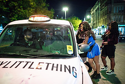 © Licensed to London News Pictures . 27/10/2018. Manchester, UK. A woman dressed up as a cheerleader gets a cab in Piccadilly Gardens in Manchester City Centre . Revellers on a night out , many in fancy dress , on the weekend before Halloween . Photo credit: Joel Goodman/LNP