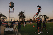 """Cheerleaders for the Bakersfield High School football team practice before a game. The words """"Driller Country"""" can be seen painted all over campus: a reference to the mascot, the Driller. Bakersfield High School is the only school in the area whose mascot reflects the oil culture of the region."""
