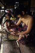 DAYAK, MALAYSIA. Sarawak, Borneo, South East Asia. Women and children. Weaving rattan sack on longhouse verandah. Tropical rainforest and one of the world's richest, oldest eco-systems, flora and fauna, under threat from development, logging and deforestation. Home to indigenous Dayak native tribal peoples, farming by slash and burn cultivation, fishing and hunting wild boar. Home to the Penan, traditional nomadic hunter-gatherers, of whom only one thousand survive, eating roots, and hunting wild animals with blowpipes. Animists, Christians, they still practice traditional medicine from herbs and plants. Native people have mounted protests and blockades against logging concessions, many have been arrested and imprisoned.