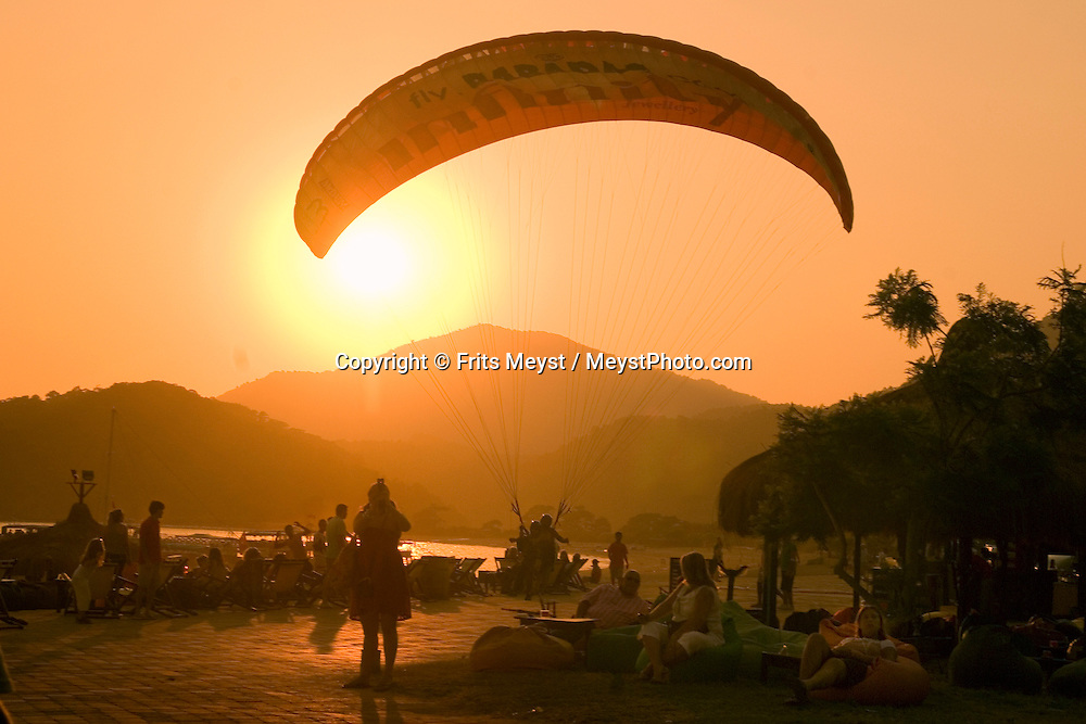 Olu Deniz, Fethiye, Mugla, Turkey, July 2008. Tandem paragliders land at sunset on the boulevard. A beach holiday at the Blue Lagoon of Oludeniz. Photo by Frits Meyst/Adventure4ever.com