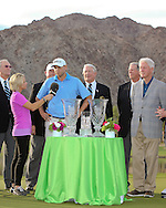 """22 JAN 15  The 42nd President of the United States, William Jefferson Clinton looks on as Bill Haas accepts the trophy on the 18th green after Sunday""""s Final Round at The Humana Challenge at PGA West, in LaQuinta, California.(photo credit : kenneth e. dennis/kendennisphoto.com)"""