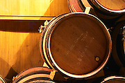 """Wooden barrels with aging wine in the cellar of Guigal in Ampuis. The barrels are stored """"bond a cote"""" (with the bung hole to the side - slightly to the left in this case), a methid favoured by some wine producers because it supposedly leads to less evaporation and less risk for oxidation.  Domaine E Guigal, Ampuis, Cote Rotie, Rhone, France, Europe"""