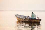 Man on boat on Ganges River contemplating sunrise