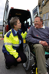 Elderly man in wheelchair is transported by amulance for a hospital appointment Yorkshire UK