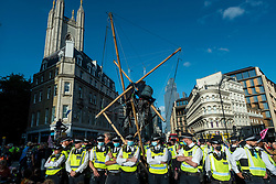 """© Licensed to London News Pictures. 27/08/2021. LONDON, UK.  Police officers surround climate activists from Extinction Rebellion who have erected bamboo scaffolding during a protest blocking traffic on Queen Victoria Street and Cannon Street in The City of London.  The event is part of the 'Impossible Rebellion' protest to """"target the root cause of the climate and ecological crisis"""" and are ongoing for two weeks until the Government agrees to stop all new fossil fuel investments.  Photo credit: Stephen Chung/LNP"""