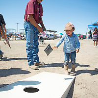 Brayleigh Chee, 2, of Leupp, Arizona participates in a bean bag toss provided by the Navajo Housing Authority as part of Kid's Day activities Thursday, Sept. 5, at the Navajo Nation Fair in Window Rock.