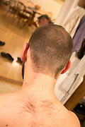 Young man shaven head home haircut in kitchen, UK - model released