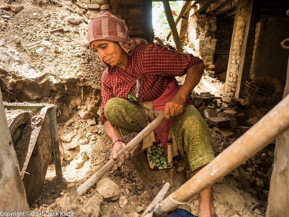 04 AUGUST 2015 - KHOKANA, NEPAL: A woman digs out her family's rice milling machine in their home in Khokana, a village about an hour from Kathmandu. Her husband was injured in the earthquake and can't work so she was digging out the milling machine, that was trapped in their house when it collapsed during the earthquake. The Nepal Earthquake on April 25, 2015, (also known as the Gorkha earthquake) killed more than 9,000 people and injured more than 23,000. It had a magnitude of 7.8. The epicenter was east of the district of Lamjung, and its hypocenter was at a depth of approximately 15km (9.3mi). It was the worst natural disaster to strike Nepal since the 1934 Nepal–Bihar earthquake. The earthquake triggered an avalanche on Mount Everest, killing at least 19. The earthquake also set off an avalanche in the Langtang valley, where 250 people were reported missing. Hundreds of thousands of people were made homeless with entire villages flattened across many districts of the country. Centuries-old buildings were destroyed at UNESCO World Heritage sites in the Kathmandu Valley, including some at the Kathmandu Durbar Square, the Patan Durbar Squar, the Bhaktapur Durbar Square, the Changu Narayan Temple and the Swayambhunath Stupa. Geophysicists and other experts had warned for decades that Nepal was vulnerable to a deadly earthquake, particularly because of its geology, urbanization, and architecture.     PHOTO BY JACK KURTZ