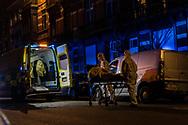 2 april 2020 Anderlecht, Brussel, België. Coronavirus interventie van ziekenauto spoed 112 mug personeel bij privé persoon thuis laat in de avond.  Ambulance personeel helemaal ingepakt tegen mogelijke besmetting haalt persoon op brancard uit appartement
