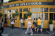 The Sun in Splendour pub on the corner of Portobello Road Market in Notting Hill, West London, England, United Kingdom. People enjoying a sunny day out hanging out at the famous Sunday market, when the antique stalls line the street.  Portobello Market is the worlds largest antiques market with over 1,000 dealers selling every kind of antique and collectible. Visitors flock from all over the world to walk along one of Londons best loved streets.