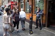 Street scene outside The Blue Posts pub on Berwick Street in Soho, London, United Kingdom.