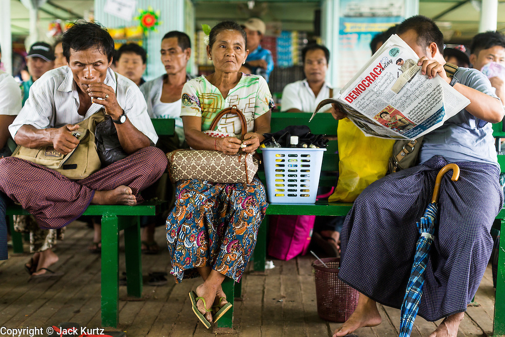 08 JUNE 2014 - YANGON, MYANMAR: A man reads a newspaper on the ferry to Dala. The ferry to Dala runs continuously through the day between Yangon and Dala. Yangon, Myanmar (Rangoon, Burma). Yangon, with a population of over five million, continues to be the country's largest city and the most important commercial center.      PHOTO BY JACK KURTZ
