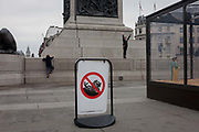 3 of 3 in a photo sequence showing children ignoring a no climbing safety sign, hauling themselves on to the plinth of Nelson's Column, on 15th December 2016, in Trafalgar Square, next to a Christmas nativity scene in London, England. The Greater London Authority (GLA) has banned tourists climbing the 148-year-old lions due to fears they are being damaged, with potentially dangerous cracks appearing as well as the indignity of having rubbish pushed in their mouths. There has also been a serious injury resulting in an air ambulance helicopter landing to evacuate to hospital in 2015.