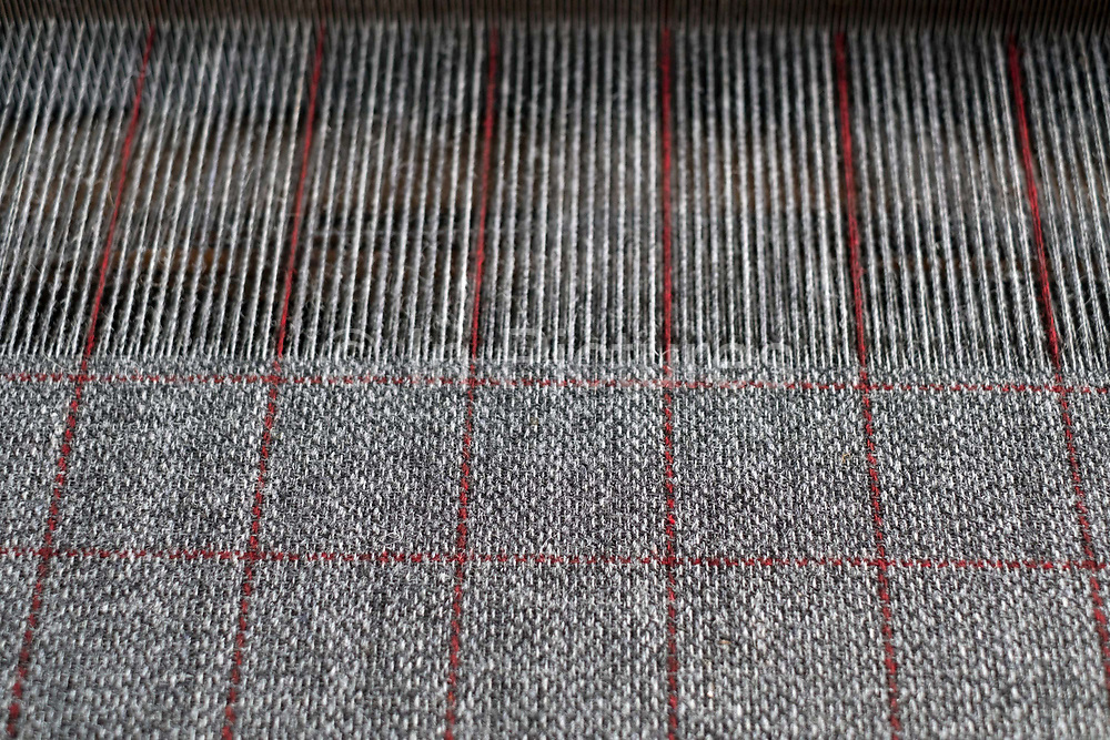 Harris tweed fabric woven on a Hattersley loom at the home of Donald MacDonald, Shawbost village, Isle of Lewis, Outer Hebrides, Scotland on 19 July 2018. Harris Tweed must be made from pure virgin wool which has been dyed and spun on the islands and handwoven at the home of the weaver in the Outer Hebrides of Scotland.