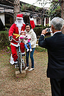 A mother and her son poses in front of a fake Santa Clauss, Cock Church, Da Lat, Vietnam, Southeast Asia