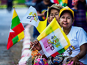 27 NOVEMBER 2017 - YANGON, MYANMAR: Women with Myanmar and Vatican flags wait to see Pope Francis on his motorcade route into Yangon. Pope Francis arrived in Yangon Monday for a four day / three night visit. Tuesday he is going to the capitol, Naypyidaw (Nay Pyi Taw) to meet with Aung San Suu Kyi and other Myanmar leaders. Wednesday and Thursday he is saying mass in Yangon and on Thursday afternoon he is going to neighboring Bangladesh. There are around 450,000 Catholics in Burma, about 1% of the total population.   PHOTO BY JACK KURTZ