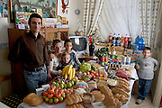 In the kitchen of their apartment in Palermo, Sicily, Italy, the Manzo family: Giuseppe, 31, Piera Marretta, 30, and their sons (left to right) Mauritio, 2, Pietro, 9, and Domenico, 7 stand and sit around a week's worth of food. From the book Hungry Planet: What the World Eats (Model Released)