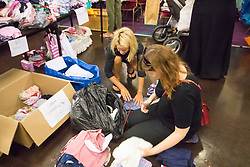London, June 14th 2017. As fire rages through a residential tower block, Grenfell Tower, in Kensington, West London, local residents show their generosity as well-wishers pour into the Maxilla Social Club with clothing, food, water and blankets for the residents of the block who will have lost everything. PICTURED: Women open the next package of clothing.